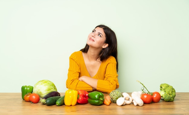 Menina adolescente com muitos legumes, olhando para cima, enquanto sorrindo