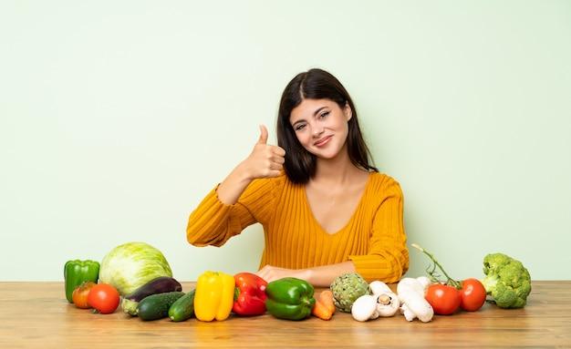 Menina adolescente com muitos vegetais com polegares para cima porque algo bom aconteceu