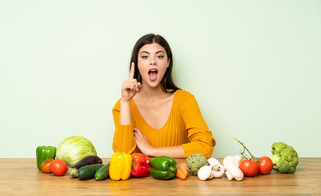 Menina adolescente com muitos vegetais pensando uma idéia apontando o dedo para cima