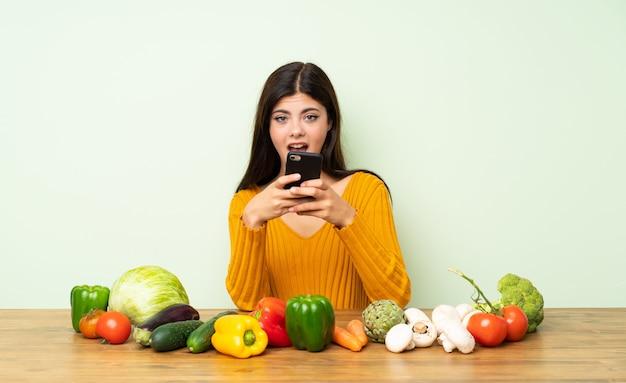 Menina adolescente com muitos vegetais surpreso e enviando uma mensagem