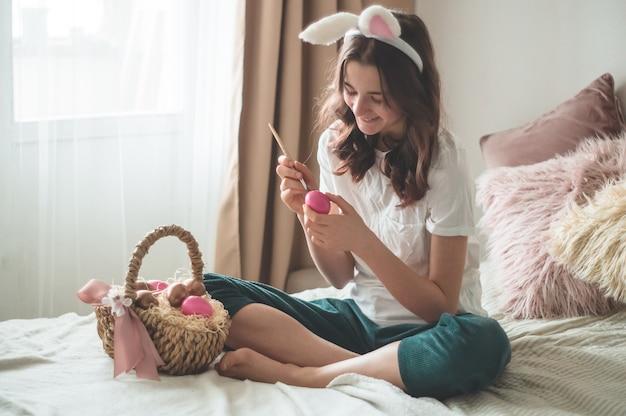 Menina adolescente com orelhas de páscoa e pinta ovos de páscoa com um pincel em uma cama em uma sala de estar