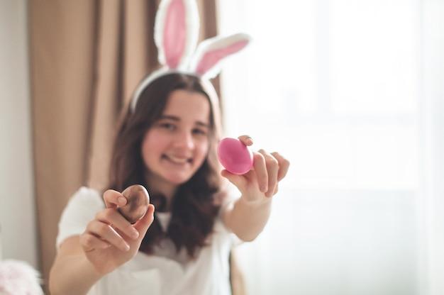 Menina adolescente com orelhas de páscoa e uma cesta de páscoa de vime em uma cama em uma sala de estar