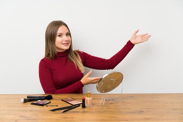 Menina adolescente com paleta de maquiagem e cosméticos em uma mesa, estendendo as mãos para o lado para convidar para vir