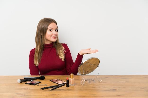 Menina adolescente com paleta de maquiagem e cosméticos em uma mesa, estendendo as mãos para o lado