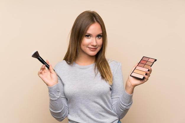 Menina adolescente com paleta de maquiagem sobre fundo isolado