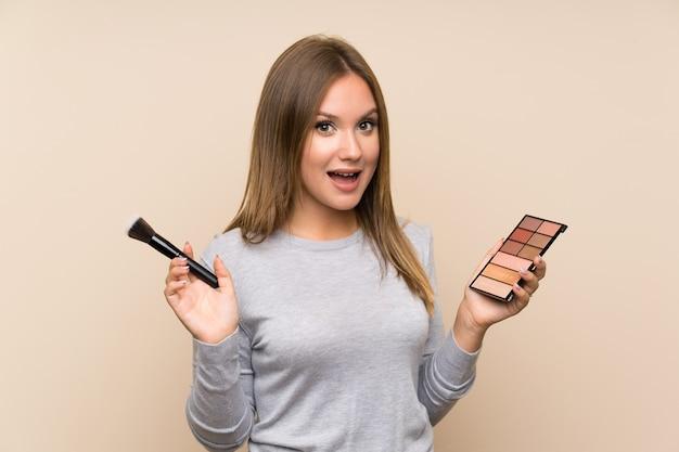 Menina adolescente com paleta de maquiagem