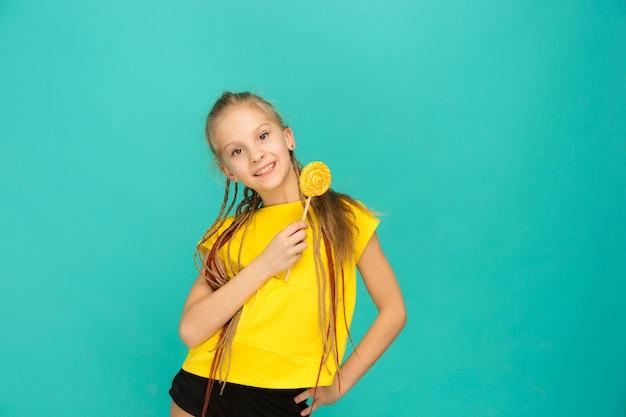 Menina adolescente com pirulito colorido em um azul