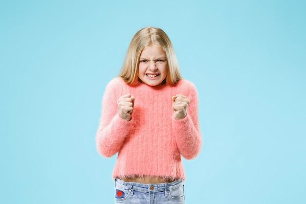 Menina adolescente com raiva em pé no estúdio azul da moda.
