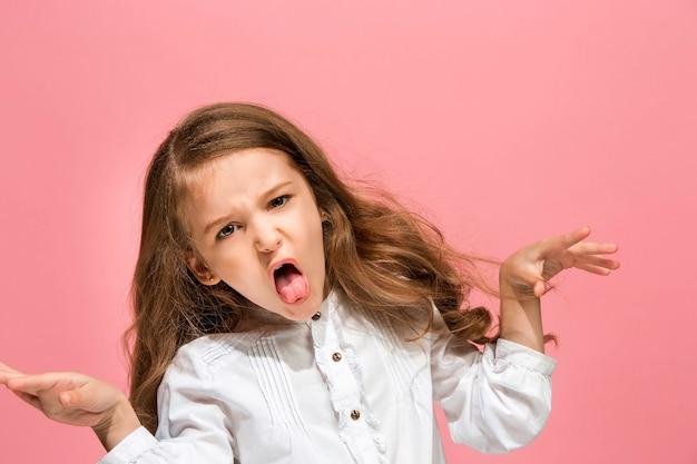 Menina adolescente com raiva em pé no fundo do estúdio azul da moda. retrato feminino de meio corpo.