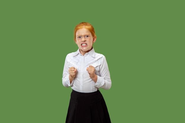 Menina adolescente com raiva em pé no fundo do estúdio verde na moda. retrato feminino de meio corpo. emoções humanas, conceito de expressão facial. vista frontal.