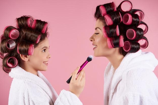 Menina adolescente com rolos fazendo maquiagem para a mãe.