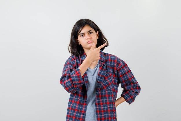 Menina adolescente com roupas casuais, apontando para o canto superior direito e olhando sombrio, vista frontal.