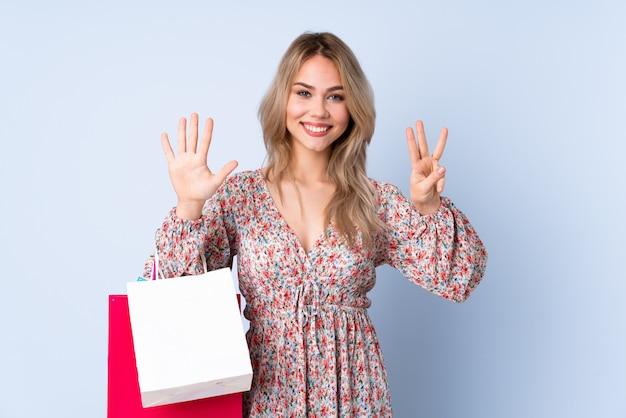 Menina adolescente com sacola de compras na parede azul, contando oito com os dedos