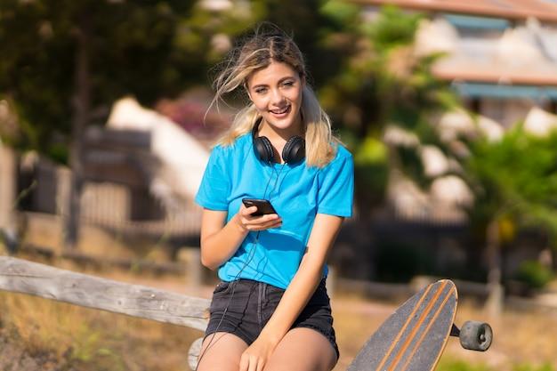 Menina adolescente com skate ao ar livre surpreso e enviando uma mensagem