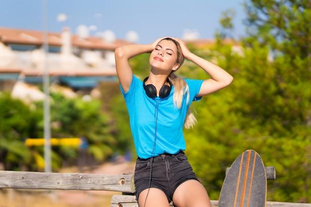 Menina adolescente com skate em sorrir ao ar livre