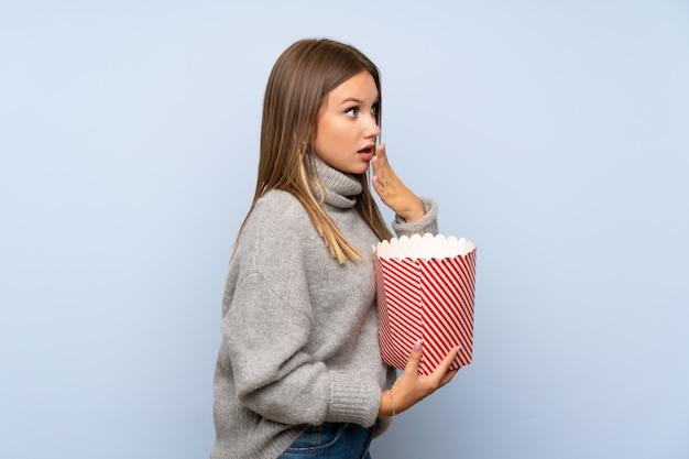 Menina adolescente com suéter segurando uma tigela de pipocas