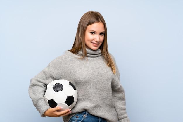 Menina adolescente com suéter sobre fundo azul isolado, segurando uma bola de futebol