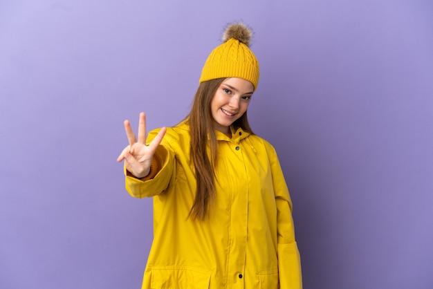 Menina adolescente com um casaco à prova de chuva sobre um fundo roxo isolado feliz e contando três com os dedos