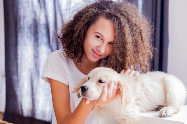 Menina adolescente com um pequeno golden retriever