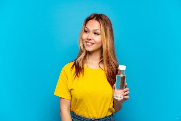 Menina adolescente com uma garrafa de água isolada olhando para o lado e sorrindo