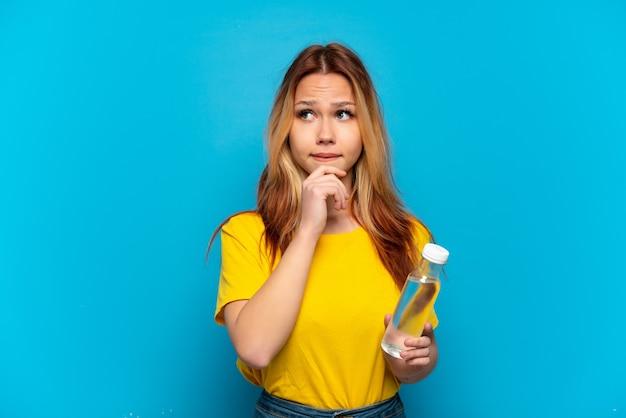 Menina adolescente com uma garrafa de água isolada, tendo dúvidas e pensando