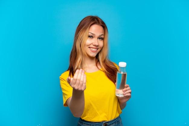 Menina adolescente com uma garrafa de água sobre fundo azul isolado, convidando para vir com a mão. feliz que você veio