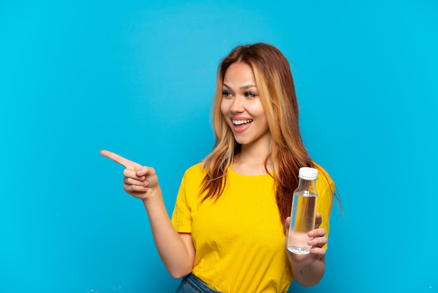 Menina adolescente com uma garrafa de água sobre um fundo azul isolado apontando o dedo para o lado e apresentando um produto