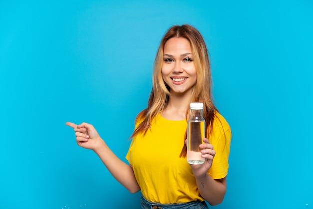 Menina adolescente com uma garrafa de água sobre um fundo azul isolado apontando para trás