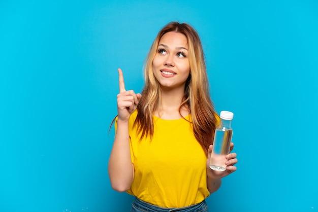 Menina adolescente com uma garrafa de água sobre um fundo azul isolado apontando uma ótima ideia