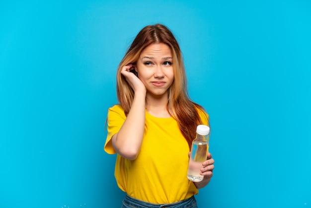 Menina adolescente com uma garrafa de água sobre um fundo azul isolado frustrada e cobrindo as orelhas
