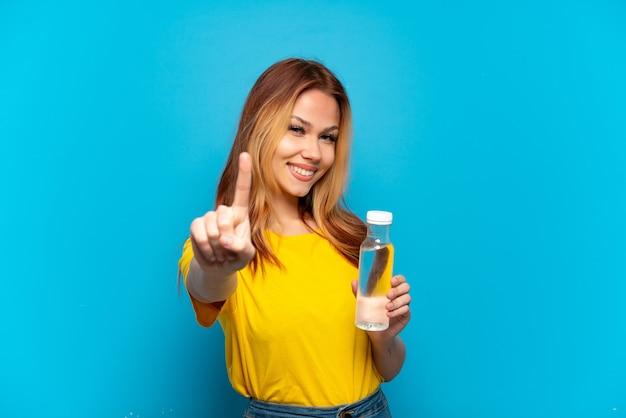 Menina adolescente com uma garrafa de água sobre um fundo azul isolado, mostrando e levantando um dedo