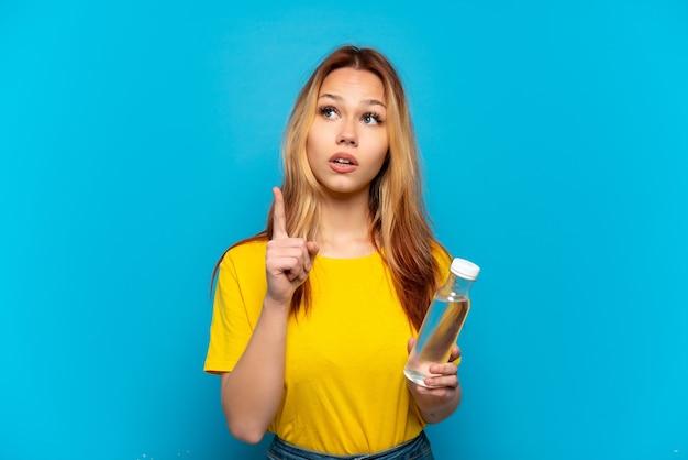 Menina adolescente com uma garrafa de água sobre um fundo azul isolado pensando em uma ideia apontando o dedo para cima