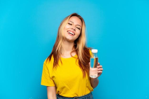 Menina adolescente com uma garrafa de água sobre um fundo azul isolado rindo