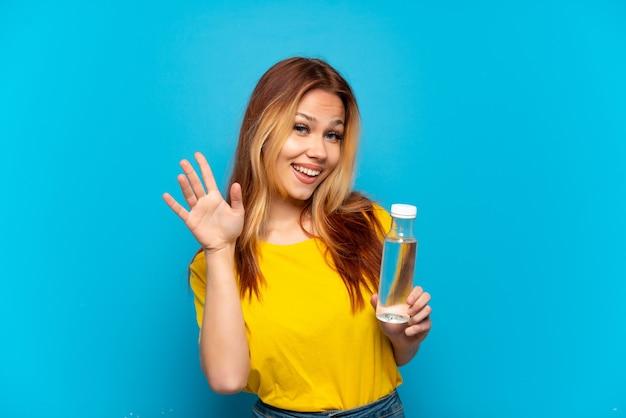 Menina adolescente com uma garrafa de água sobre um fundo azul isolado saudando com a mão com expressão feliz