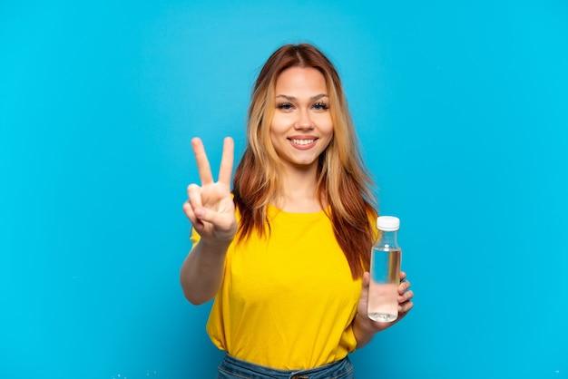 Menina adolescente com uma garrafa de água sobre um fundo azul isolado sorrindo e mostrando o sinal da vitória