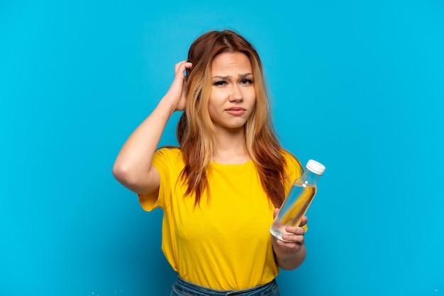 Menina adolescente com uma garrafa de água sobre um fundo azul isolado, tendo dúvidas