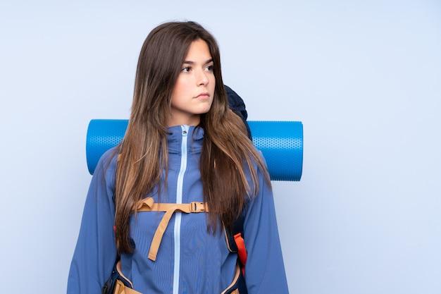 Menina adolescente com uma mochila de alpinismo sobre parede azul