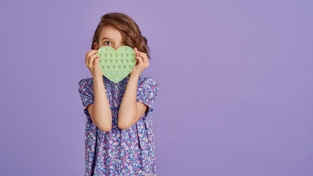 Menina adolescente com vestido estampado de flor azul de verão segurando um brinquedo anti-stress em lavanda