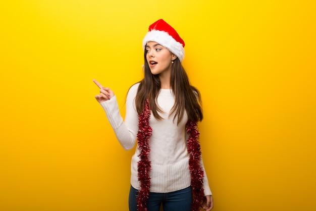 Menina adolescente comemorando feriados de natal, apontando o dedo para o lado e apresentando um produto
