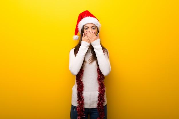 Menina adolescente comemorando feriados de natal, cobrindo a boca com as mãos