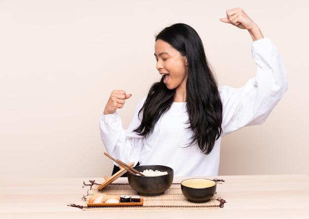 Menina adolescente comendo comida asiática isolada em bege comemorando uma vitória