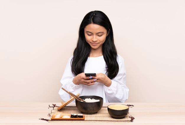 Menina adolescente comendo comida asiática isolada em bege, enviando uma mensagem com o celular