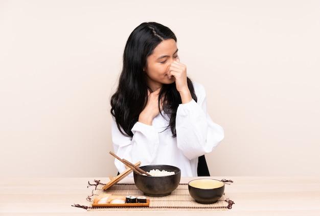 Menina adolescente comendo comida asiática isolada em bege está sofrendo com tosse e se sentindo mal