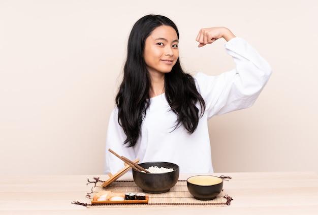 Menina adolescente comendo comida asiática isolada em bege, fazendo um gesto forte