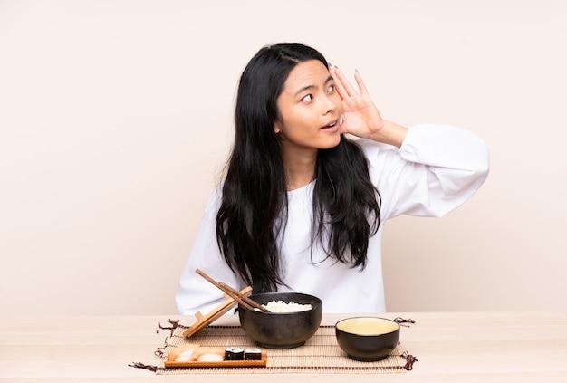 Menina adolescente comendo comida asiática isolada em bege, ouvindo algo, colocando a mão na orelha