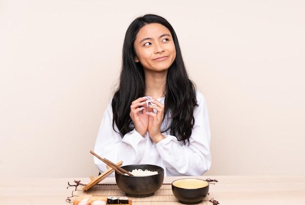 Menina adolescente comendo comida asiática isolada em bege, planejando algo