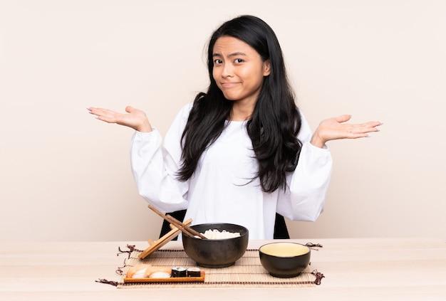 Menina adolescente comendo comida asiática isolada em bege, tendo dúvidas ao levantar as mãos