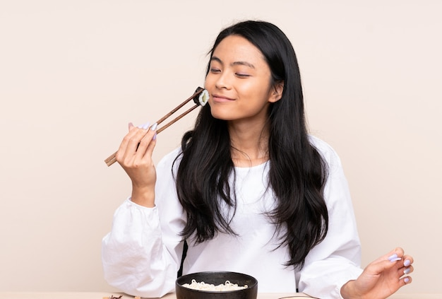 Menina adolescente comendo comida asiática isolada em bege