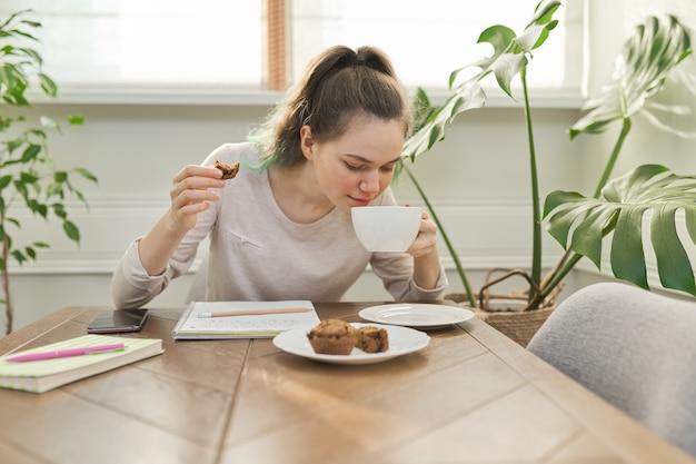Menina adolescente comendo cupcakes, bebendo chá, sentada à mesa em casa