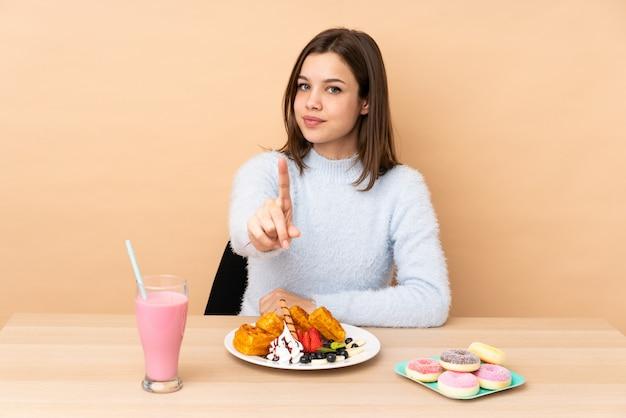 Menina adolescente comendo waffles isolados na parede bege, mostrando e levantando um dedo